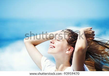 Young beautiful woman with streaming hair in front of the ocean - stock photo