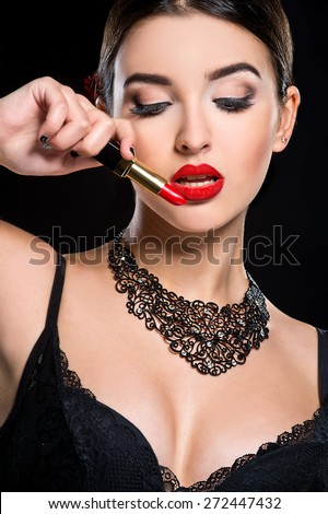 young beautiful woman with stylish make-up and red lipstick in her hand - stock photo