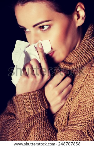 Young beautiful woman with tissue. On black background. - stock photo