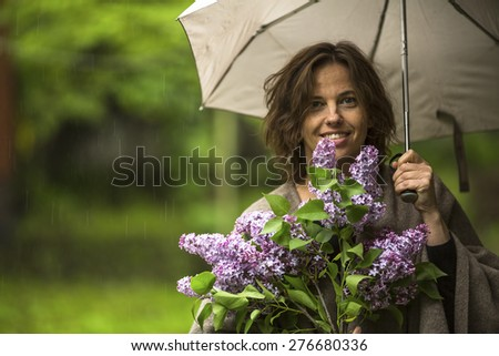 Young beautiful woman with umbrella and branch of lilac, outdoors in the rain. - stock photo
