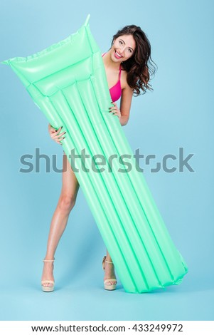 Young beautiful woman with yellow mattress is going to swim isolated on the blue background - stock photo