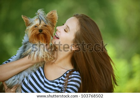 Young beautiful woman with Yorkshire Terrier, against green of summer park. - stock photo