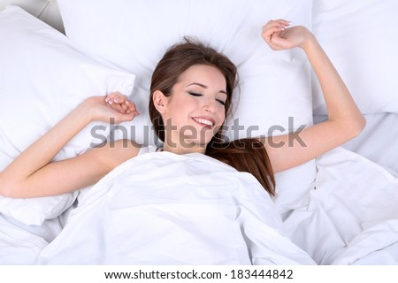 Young beautiful woman woke up in bed close-up - stock photo