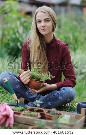 Young beautiful woman working in the garden, planting young seedling