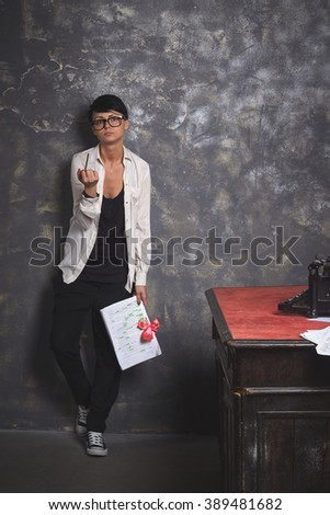 Young  beautiful woman writer in creative process, reading her work, writing article, art space with grey background - stock photo