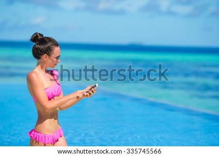 Young beautiful woman writing message on white beach - stock photo