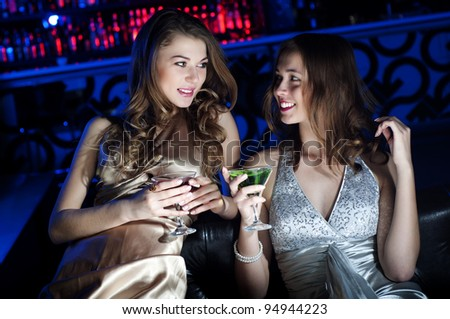 Young beautiful women, have a rest on a sofa and drink beverages - stock photo