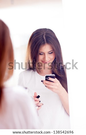Young beautiful women lady touching and browsing her smart phone at home. In the Mirror. - stock photo