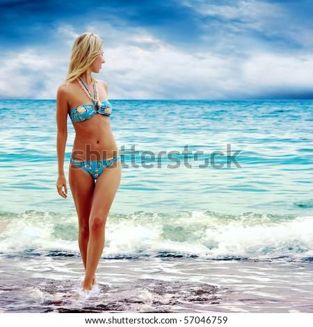 Young beautiful women on the sunny tropical beach in bikini - stock photo