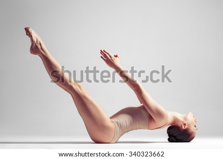 young beautiful yoga female posing on a studio background - stock photo