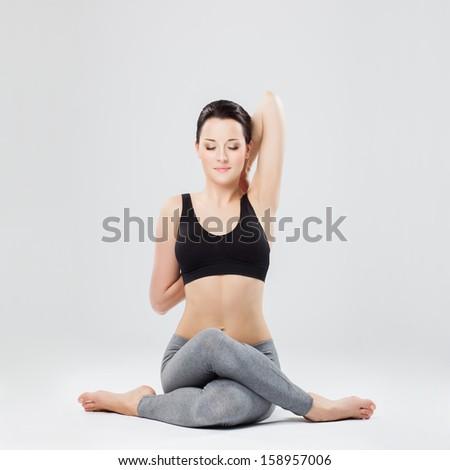 young beautiful yoga posing  on a studio background - stock photo