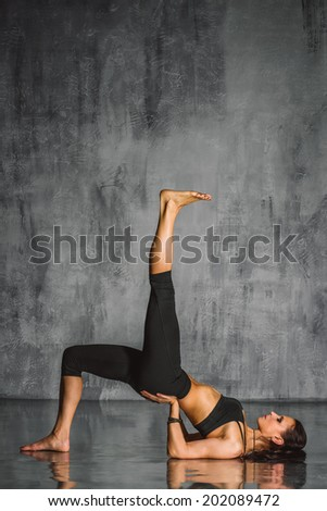 young beautiful yoga posing on a studio background - stock photo