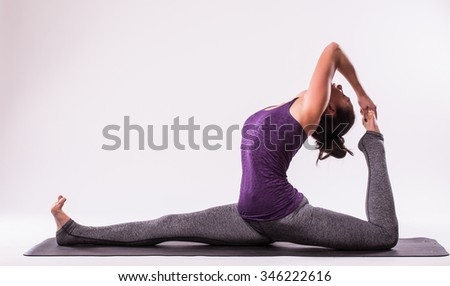 young beautiful yoga woman posing on a studio background - stock photo
