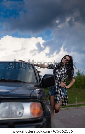 Young beautisul woman with long hair and in cool jeans briefs on her head is standing near a black car.