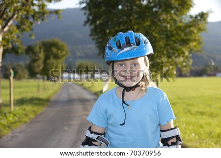 Young beautiul blond girl inline-skating outdoor. - stock photo