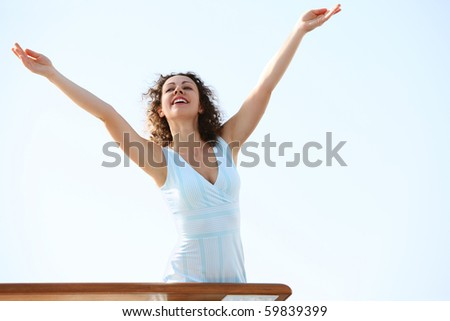 young beauty brunette woman standing on cruise liner deck, putting hands up