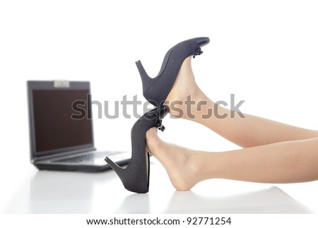 Young Beauty business woman take off her high heels shoes in office - stock photo