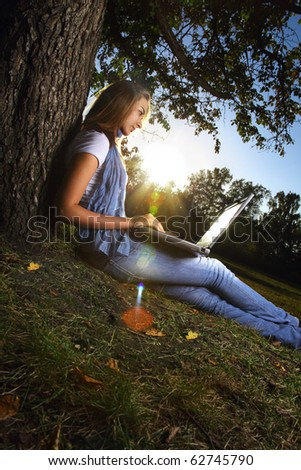 young beauty girl with laptop in park, photo with artistic lens flare effect - stock photo