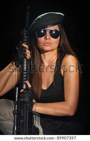 young beauty girl with machine-gun on black background - stock photo