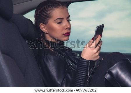 Young beauty girl with mobile phone driving car. - stock photo