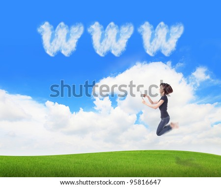 Young beauty happy jump and using tablet pc in the air on meadow with www cloud sky background , model is a cute asian, for cloud computing concept - stock photo
