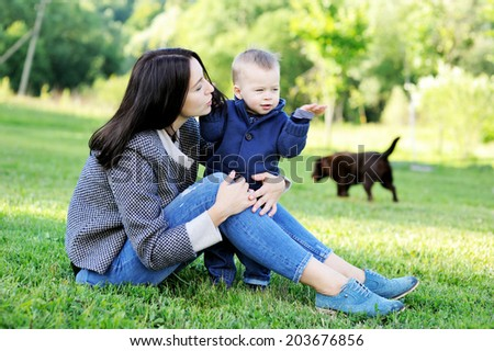 Young beauty mother hugs her cute baby son outdoors on the green lawn in the park - stock photo