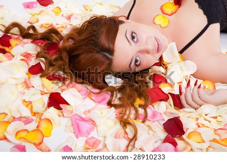 young beauty sensual woman with long hair lying on petal - stock photo