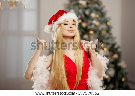 Young beauty smiling santa woman near the Christmas tree. Fashionable luxury girl celebrating New Year. Beautiful luxury trendy blonde. Thumbs up - stock photo