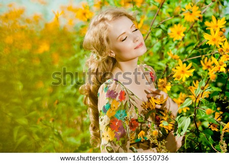 Young beauty smiling woman in the blooming garden with flowers. Girl resting on the  outside.  - stock photo