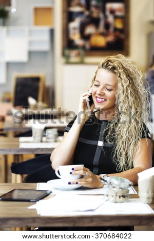 Young beauty smiling woman sitting in a cafe and talking on the cellphone - stock photo