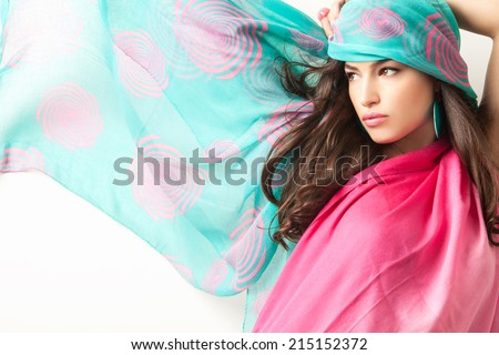 young beauty with blue pink scarf over her head, studio shot - stock photo