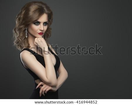 Young beauty woman fashion studio shot on dark background - stock photo