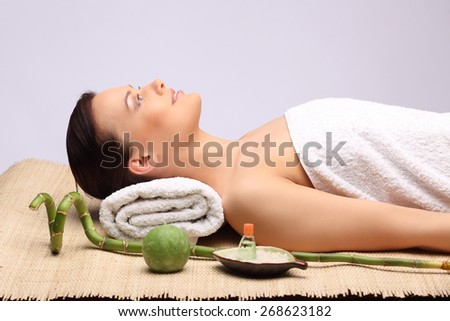 Young beauty woman in a spa with closed eyes studio