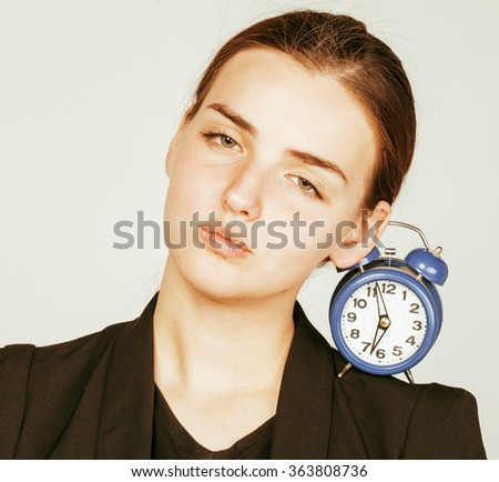 young beauty woman in business style costume waking up for work early morning on white background with clock dreanking coffee close up