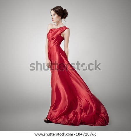 Young beauty woman in fluttering red dress. - stock photo