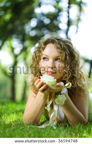 young beauty woman in park with flower rose