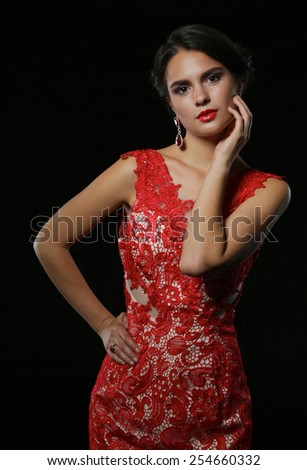 Young beauty woman in red dress. Isolated on black background - stock photo