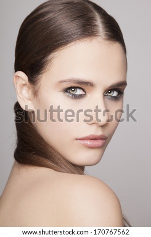 Young beauty woman looking at the camera. Grey background. - stock photo