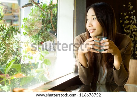 Young beauty woman looking out of the window  and holding a glass of water in the restaurant - stock photo