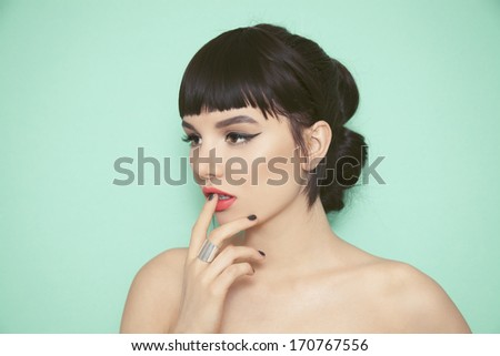 Young beauty woman with fringe, black nails and big silver ring touching her lips. Green background. - stock photo