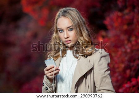 Young beauty woman writing message on cell phone in a autumn park - stock photo