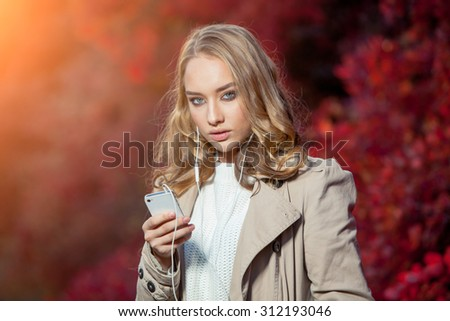 Young beauty woman writing message on cell phone in a autumn park. - stock photo