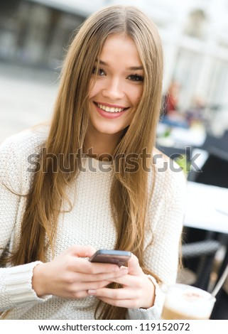 Young beauty woman writing message on cell phone in a street cafe. Looking at camera - stock photo
