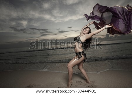 Young belly dancer on the beach with a veil - stock photo