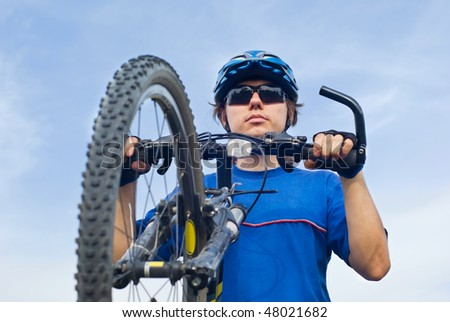 young bicyclist in helmet on a blue sky background - stock photo