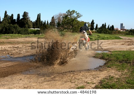 Young biker riding through a muddy puddle creating a splash - stock photo