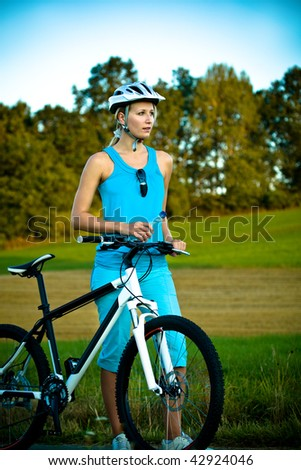 young biking woman having rest in the field - stock photo