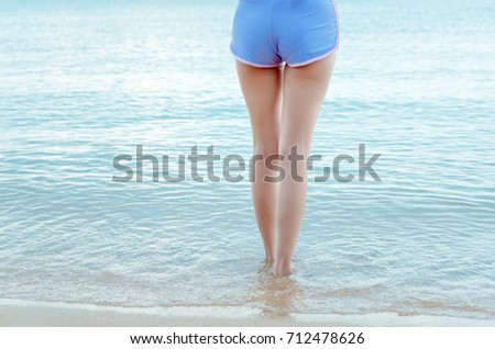 stock photo young bikini girl sitting on white sand at beach seaside with hat in holidays relaxing vacation 712478626
