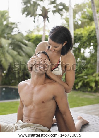 Young bikini woman covering shirtless man's eyes outdoors - stock photo