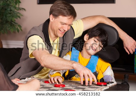 Young biracial disabled boy in wheelchair playing checkers with father at home - stock photo